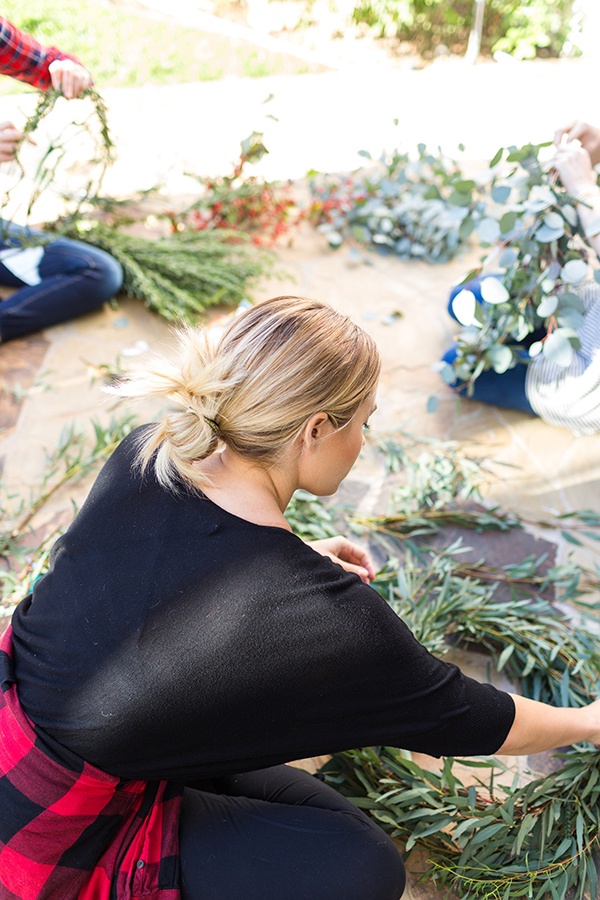 DIY your own holiday wreath with fresh greens and blooms.