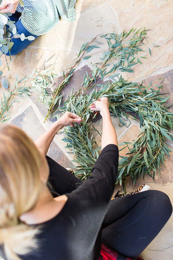 Fastening greenery to wire wreath bases.