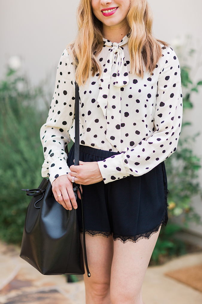 Dotted bow-neck blouse, lace shorts, and bucket bag